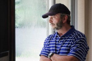 Adult Male Ponders Future Looking Out Rain Covered Window